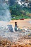 En barnflicka spelar i högar av avfall, medan hennes moder bränner det på stranden av Kollam, Kerala Royaltyfria Foton