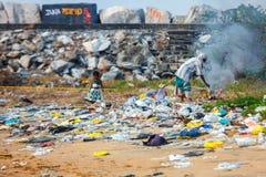 En barnflicka spelar i högar av avfall, medan hennes moder bränner det på stranden av Kollam, Kerala Royaltyfria Bilder
