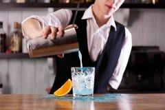 En bartender förbereder en blå laguncoctail arkivbilder