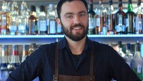 En bartender på arbete som ler och ser kameran Arkivfoto
