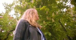 En bas du tir supérieur de la position blonde assez caucasienne d'étudiant en parc vert observant la beauté de la nature clips vidéos
