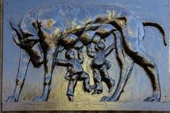 En basrelief som visar henne vargen som matar två affärsmän (romulus Arkivbilder