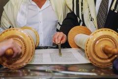 En be man med en tefillin på hans arm och huvud som rymmer en Torah, medan läsa en be på en judisk rituell bar mitzwahceremoni Arkivfoton