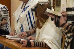 En be ung man med en tefillin på hans arm och huvud som rymmer en bibelbok, medan läsa en be Royaltyfri Bild