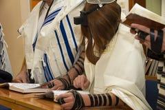 En be ung man med en tefillin på hans arm och huvud som rymmer en bibelbok, medan läsa en be på en judisk ritual Arkivfoto