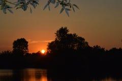 En beautifal solnedgång och en sjö Arkivfoto