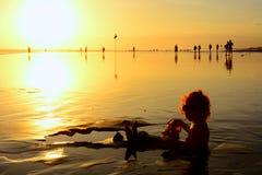 En bebé divertido de la playa de la puesta del sol siéntese en la arena mojada negra y el arrastre a la resaca del mar para nadar fotografía de archivo