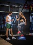 En bedöva flicka som utarbetar med ett gradvist i en idrottshallbakgrund En kvinnautbildning med en ung lagledare i en konditionk arkivfoton