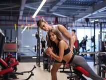 En bedöva kvinna som gör övningar på en simulator på en idrottshallbakgrund Sport, kondition, livsstil och folkbegrepp royaltyfria bilder
