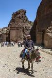 En beduin som pojken rider en åsna till och med det forntida, fördärvar av Petra i Jordanien arkivfoton