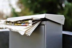 En begreppsbild av en brevlåda med en tidning Royaltyfria Bilder