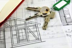 En begreppsbild av ett husplan och med tangent Arkivfoto