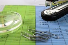 En begreppsbild av en finansiell rapport med ett exponeringsglas Arkivfoton