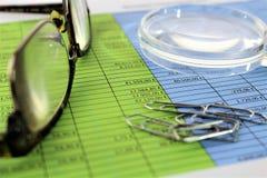 En begreppsbild av en finansiell rapport med ett exponeringsglas Arkivbilder