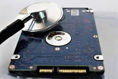 En begreppsbild av en hårddisk, skivan och en stetoskop arkivfoto