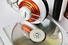 En begreppsbild av en headphone med en musikCD Arkivbild