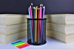 En begreppsbild av några färgrika blyertspennor med några böcker Fotografering för Bildbyråer