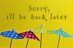 En begreppsbild av några paraplyer med texten, ledsen iska vara tillbaka senare royaltyfri foto