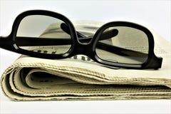 En begreppsbild av en tidning med exponeringsglas Arkivfoton