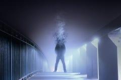 En begreppsmässig digital konstbild av en man, som är huvudet, har desintegrerat och har vänt in i rök som står på en dimmig bana arkivbilder