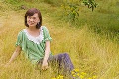 En behagfull flicka med yelloeogräs Arkivbild