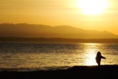 En behandla som ett barnflicka som spelar på stranden på solnedgången: Guld- trädgårdar parkerar, Seattle USA Royaltyfri Fotografi