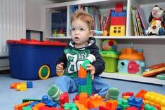 En behandla som ett barnpojke som spelar med plast- kvarter Royaltyfria Bilder