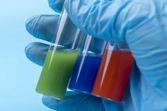 En behandskad hand rymmer tre små medicinflaskor av olik flytande inom på en blå bakgrund royaltyfria foton