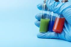 En behandskad hand rymmer tre små medicinflaskor av olik flytande inom på en blå bakgrund royaltyfri fotografi