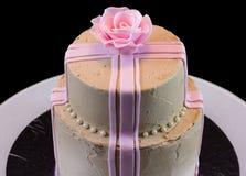 En beige kaka med en rosa färgros Arkivfoto