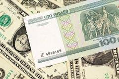 En Belorussian rubelsedel med amerikanen en dollar räkningar arkivbild