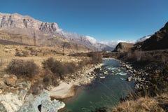 En bergflod i ett near bergigt stenigt område, som där är kraftledningar på bakgrunden av epos, vaggar och en blått arkivbilder
