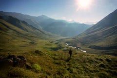 En bergturist går raksträckan till solen Denna är en mycket spännande resa Arkivbilder