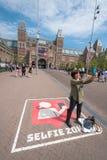En besökare i Amsterdam tar en selfiebild med Rijksmuseumen i bakgrunden royaltyfria bilder