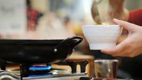 En besökare på en koreansk restaurang häller ut hans mat Maträtten värmas med en liten gasugn Autentisk koreansk kokkonst stock video