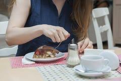 En besökare till ett kafé äter händer för en efterrätt, anordningar som tjänar som royaltyfria bilder