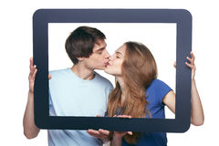 En besarse del marco de la tableta de la tenencia de los pares del amor Imagen de archivo