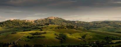 En beskåda av en town av tuscany i det ljust av en solnedgång Arkivfoto