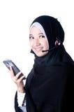 En beslöjad kvinna meddelar genom att använda mobiltelefoner Royaltyfria Foton