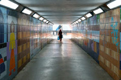En beslöjad kvinna som bara går i en dunkel fot- gångtunnel arkivbilder