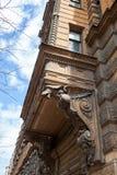 En beståndsdel av fasaden av en Art Nouveau byggnad med basrelief och statyer royaltyfri foto