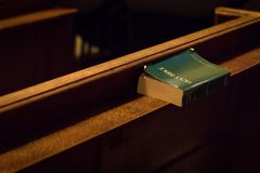 En bibel lämnade på en kyrkbänk i Sts James kyrka, London, UK royaltyfria bilder