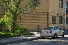 En bil och ett träd utanför i solig dag Arkivfoton