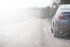 En bil på en lantlig väg i den första höstsnön Den första vintern royaltyfri bild