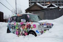 En bil som fylls med tecknad filmklistermärken, begravas till hälften av snön, den Otaru staden, Hokkaido, Japan royaltyfri fotografi