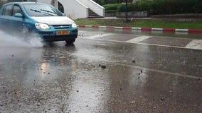 En bil som plaskar vatten från en pöl av vatten stock video