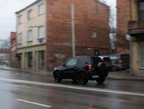 En bil som rusar till och med gatan arkivbild