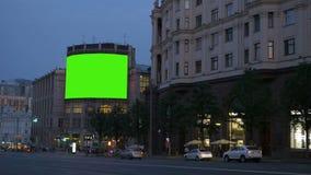 En Bilboard med en grön skärm på en upptagen gata lager videofilmer
