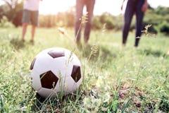 En bild av bollen som ligger i gräs Det finns medlemmar av en familj som spelar med det De är klara att skjuta bollen De är Royaltyfri Foto