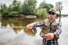 En bild av den kalla grabben står i vatten och fiske Han rymmer fluga-fiske med rullen under den i en hand och sked från den royaltyfri foto